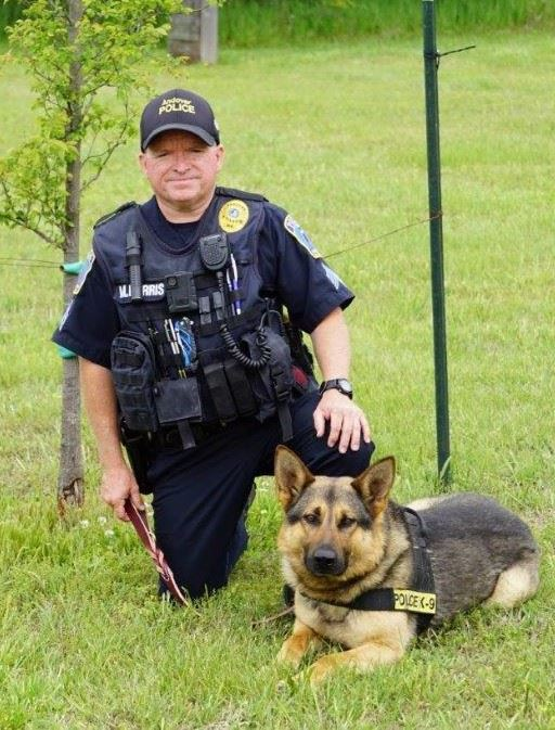 Sgt Farris kneeling next to K-9 Roko